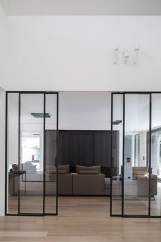 Beautiful steel sliding doors. Project VL by Dennis T'Jampens. Photo by Cafeïne|Thomas de Bruyne. Dekru iron framed doors taatsdeuren stalen deuren pivot deuren steel doors