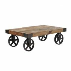 """Solid wood coffee table with antiqued metal wheels.    Product: Coffee tableConstruction Material: Solid wood and metalColor: Distressed naturalFeatures: Will enhance any decor Dimensions: 13.8"""" H x 43.3"""" W x 28"""" DCleaning and Care: Wipe clean with a dry cloth"""