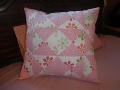 A patchwork quilted pillow cushion made of muslin cotton fat quarter materials.