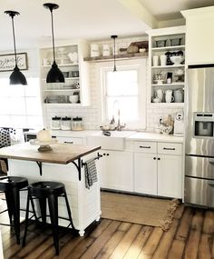 White farmhouse kitchen, subway tile, butcher block, open cabinets.