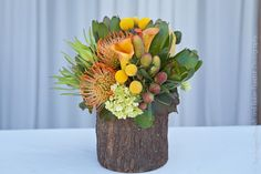 Orange pincushion protea, yellow billy balls, orange calla lilies in a rustic wood container.  An Aspen Branch Original. www.aspenbranch.com