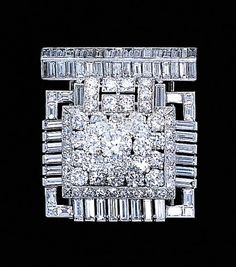 A fine diamond clip Art Deco brooch, by CARTIER. Designed as a circular-cut diamond stylised pyramid within a baguette-cut diamond openwork surround to the diamond-set arched bar top, circa 1932. Signed by Cartier, London, nos. 7881 and 133. (hva)