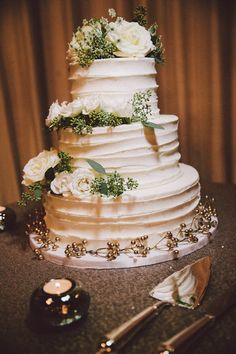 Queen Anne's Lace and white roses effortlessly transformed a simple wedding cake into a three-tiered chic masterpiece. | White Wedding Cake | Speakeasy Themed Industrial Wedding | Zorz Studios