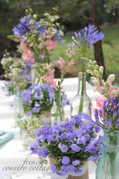 FRENCH COUNTRY COTTAGE:Little pots of campanula with vases of snapdragons and agapanthus
