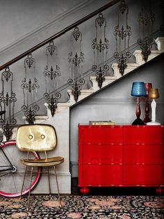 veloisto:  rojo y oro. love the dresser under the stairs.