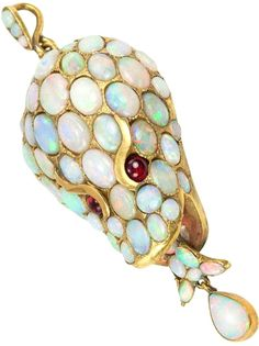 Opal Snake Head Pendant Circa 1870.  A unique and whimsical Victorian snake head pendant! The snake head is covered in opals with ruby cabochon eyes in 15 karat yellow gold, circa 1870.