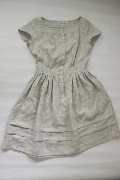 Here is a dress that might have been worn going to the seaside on a cloudy summer day sometime in the 19th century. I like to think of Anne of Green Gables wearing this dress; reading a book or simply daydreaming on Prince Edward Island. It is made of the most lovely light weight cream and taupe striped linen. It has mother of pearl buttons that run up the front placket and two tucks at the hem of the skirt. The waist is fitted to the natural waistline. There are pockets on either side of…