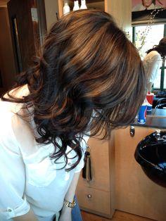 Dark hair with Carmel highlights and curls