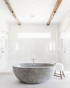 White and bright modern master bathroom design with free standing concrete tub and large master shower with separate entrances and dual shower heads with ceiling wood beams - Modern Nest