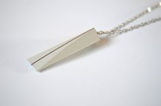 This is a unique, elegant concrete necklace with silver stripe on silver chain. Each pendant is handmade, made of fine, high quality, gray concrete with shiny surface. Details: - Pendant: ca. 4,5 cm * 1,3 cm - Chain: ca. 70 cm long The necklace can be made in other forms or colors, so feel free to contact me, every individual requests are weolcome.