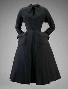"""Day Dress, Christian Dior, France: 1948, wool melton. """"Dior dominated the world of fashion for a decade- from the spectacular appearance of the New Look in 1947 to his sudden death in 1957. Dior's Zig-Zag collection of 1948 aimed to 'give the figure the animated look of a drawing.' This dress, for example, features a flaring shoulder line, turned-back cuffs, and exaggerated pockets."""""""