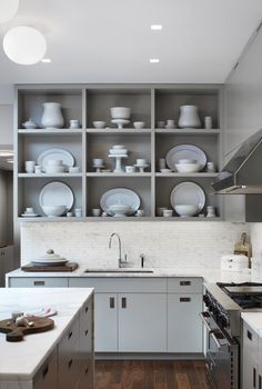 Open shelves, painted medium gray, with white china displayed | Remodelista