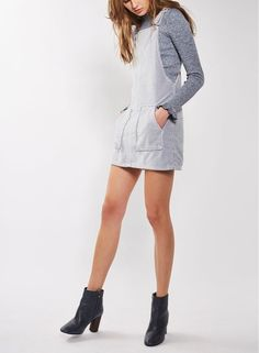Elegant velvet goes quirky and chic as an overall-style pinafore dress fronted by two darling patch pockets.