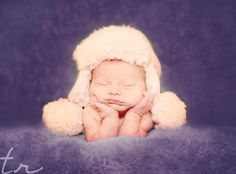 Newborn hands under chin with fluffy winter hat.