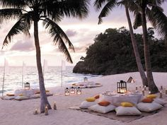 We love this beach wedding reception complete with mats, low tables and cushioned seats!