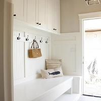In the Fun Lane - laundry/mud rooms - mudroom, mudroom storage, mudroom built-ins, mudroom bench, built-in bench, built-in mudroom bench, mudroom coat hooks, beadboard, beadboard mudroom, mudroom cabinets, mudroom cupboards, gray tiled floor, gray tile, white mudroom built-ins, greige walls, greige wall color, iron hardware, Filament Pendant, mud room, beadboard bench, white beadboard bench, mudroom bench, mud room bench, mud room pendant, mud room lighting, row of hooks,