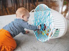 Usando um cesto de roupas de plástico, alguns objetos de diferentes cores, formas e texturas e fio de malha é possível criar uma brincadeira para os bebês.