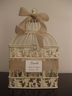 I like using an ivory or white bird cage for winter weddings. You can accent with a bow of bright colors