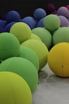 Uma das áreas comuns da feira, lotada de pufes coloridos da Lina