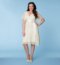 """Kiyonna Plus Size Clothing """"Lace Confections"""" Wedding Dress (Style #19120902), $248 via Kiyonna.Com --- This beautiful dress embodies retro-glam Old Hollywood style with a flattering empire waist & A-line skirt. You'll love the simple detailing of the removable satin sash and rhinestone & pearl encrusted brooch. The delicate stretch scalloped lace skims over your curves for a comfortable fit & a surplice neckline and sheer lace flutter sleeves give just the right amount of coverage."""