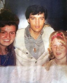 """Elvis Presley is pictured with fans outside his home at 565 Perugia Way in Bel Air, Los Angeles, CA on Sunday, May 16, 1965. The young woman on the left is Jillayne Stark (to Elvis's right). This photo was taken for her with her camera according to Cricket Coulter. Note Elvis is wearing his 10 karat gold """"Tree of Life """" pendant that was given to him by some of his friends on his 30th birthday."""