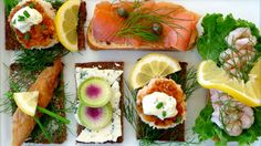 An assortment of Danish open-face sandwiches, or smorrebrod, on a white platter