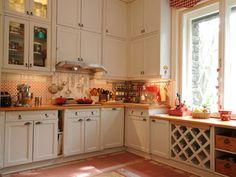 Az egyszerű, hagyományos fehér fabútor meghitt, otthonos hangulatot áraszt. A tömör fa munkalap, a pohártartó és a régi fűszeres és teás dobozok stílusos kiegészítők.