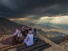 Men chat on a Sarawat Mountain overlook while sun rays create a dramatic sky over Mecca in this National Geographic Photo of the Day.