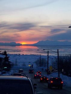 Motorists pause to take in a March sunset over Cook Inlet.