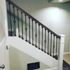 Wrought iron stair balusters with double twist and single basket.  White Newell posts and custom white oak gray stained handrail and stair treads