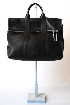 """3.1 Phillip Lim  31 Hour Bag  $750.00  Leather bag. Two rounded top handles. Foldover top flap with zip around closure. Single compartment with inner zip pocket. Topstitched edge detail throughout. Silver hardware. Unlined raw leather interior. Approximate bag dimensions: 18""""W x 12.5"""" H x 6.25"""" D. Handle drop: 4.5""""."""