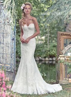 Rita wedding dress by Maggie Sottero | Simplistic elegance is found in this lace fit and flare wedding dress, sprinkled with glittering Swarovski crystals. Finished with sweetheart neckline and covered buttons over zipper and inner elastic closure. Detachable beaded lace cap-sleeves sold separately.