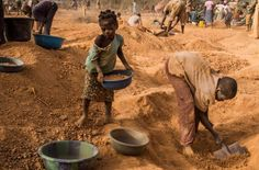 Four-year-old Rasmata Ouedraogo, left, and another child sort pans of soil for sifting. Image by Larry C. Price. Burkina Faso, 2013.