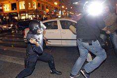 Un policía antidisturbios carga contra un grupo de personas en el entorno del Instituto Lluís Vives, en Valencia.  KAI FÖRSTERLING (EFE)