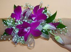 FREE CORSAGE TUTORIALS http://www.wedding-flowers-and-reception-ideas.com/how-to-make-a-corsage.html Stunning purple dendrobium blooms are a contrast against the white baby's breath and sheer silver ribbon. Accented with wired rhinestones. Learn how to make your own corsages and boutonnieres using professional florist supplies!