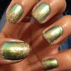 Green nails with gold glitter tips.