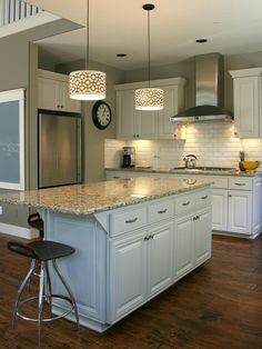 Geometric-patterned pendant lights illuminate the gray granite countertops on this large kitchen island. Dark-stained wood floors provide appealing contrast to the white cabinetry and backsplash.