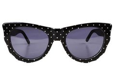 Black and white dotted sunglasses featuring cat eye frames and dark lenses.