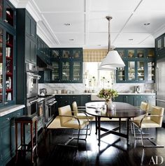 In the Houston home of decorator J. Randall Powers, Knoll's Brno chairs surround an antique table in the kitchen, where Powers paneled the ceiling and installed cabinets whose rich gray-green hue gives the space a sense of intimacy   archdigest.com
