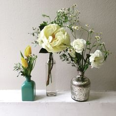 Mixed glass bottles with yellow tulips, yellow peonies, and chamomile