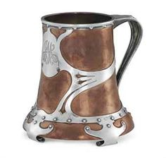 An Art Nouveau Silver and Copper Mug, with a mark under base on copper edge of Thomas G. Brown & Sons, New York, Circa 1900.  Inverted bell form on four scroll feet, copper body with silver whiplash mounts attached with circular slver rivets, engraved with the monogram JM, the bottom of cut glass.:  Christie's