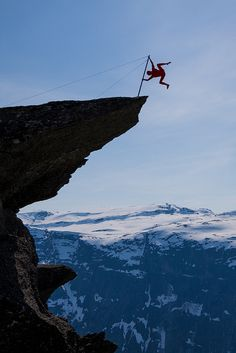 Eskil Rønningsbakken, a Norwegian artist, is doing a balancing act on the tip of the Trolltunga, Hardanger fjord, Norway. There is about 300 meters to the ground under him. Photo by Dag Endre Opedal