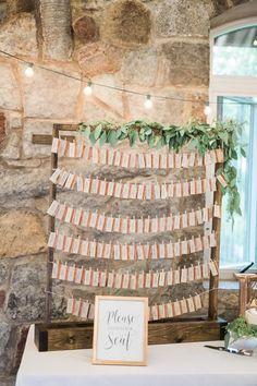 Elegant wedding escort card idea - wooden escort card display with cards hung on clothespins + greenery {Rockhill Studio}