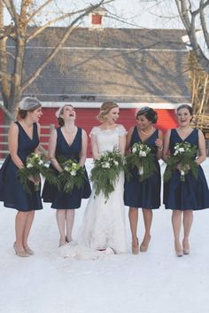 Winter bride wit her navy blue bridesmaids…
