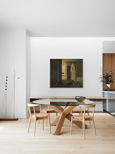 A neutral dining space is complemented by the warmth of wood and a striking still-life painting.