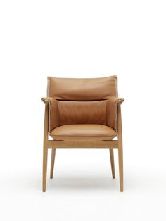 A contemporary-modern lounge chair and ottoman  that recall Scandinavian modernism. From designer furniture brand Carl Hansen & Son. The Embrace Lounge Chair by Austrian design studio EOOS. Shown here in leather.