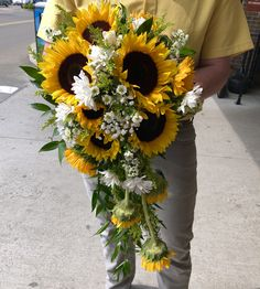 Country cascading bridal bouquet with sunflowers, daisies, solidago, baby's breath and Italian ruscus