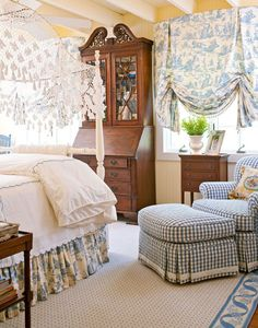 Country French details abound in this girl's bedroom, which is accented with blue-and-white fabrics. Toile shades and a matching bedskirt are a classic touch; gingham fabric on the armchair and ottoman are trimmed in ribbons of ivory for a polished look. The area rug from Stark ties the room's blue-and-white fabrics together. via TraditionalHome.com