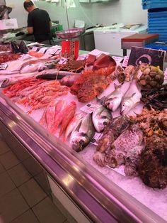 Este es un foto de los pescados en una pescadería. Hay muchos pescados diferentes y huele muy mal.