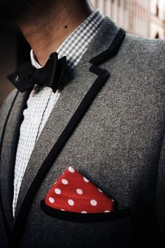 Grey woollen blazer with black piping detail, grey gingham shirt, Ralph Lauren Rugby bow tie, red and white polka dot pocket square